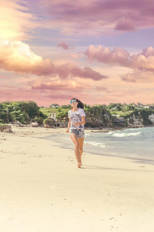 woman running on sea shore near body of water
