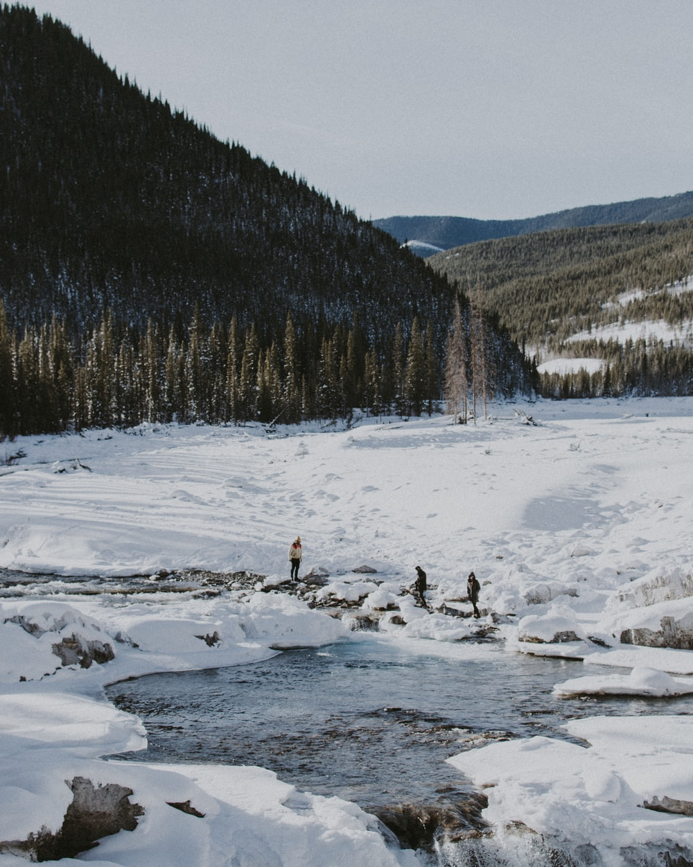 three people standing on snow near body of water during daytim