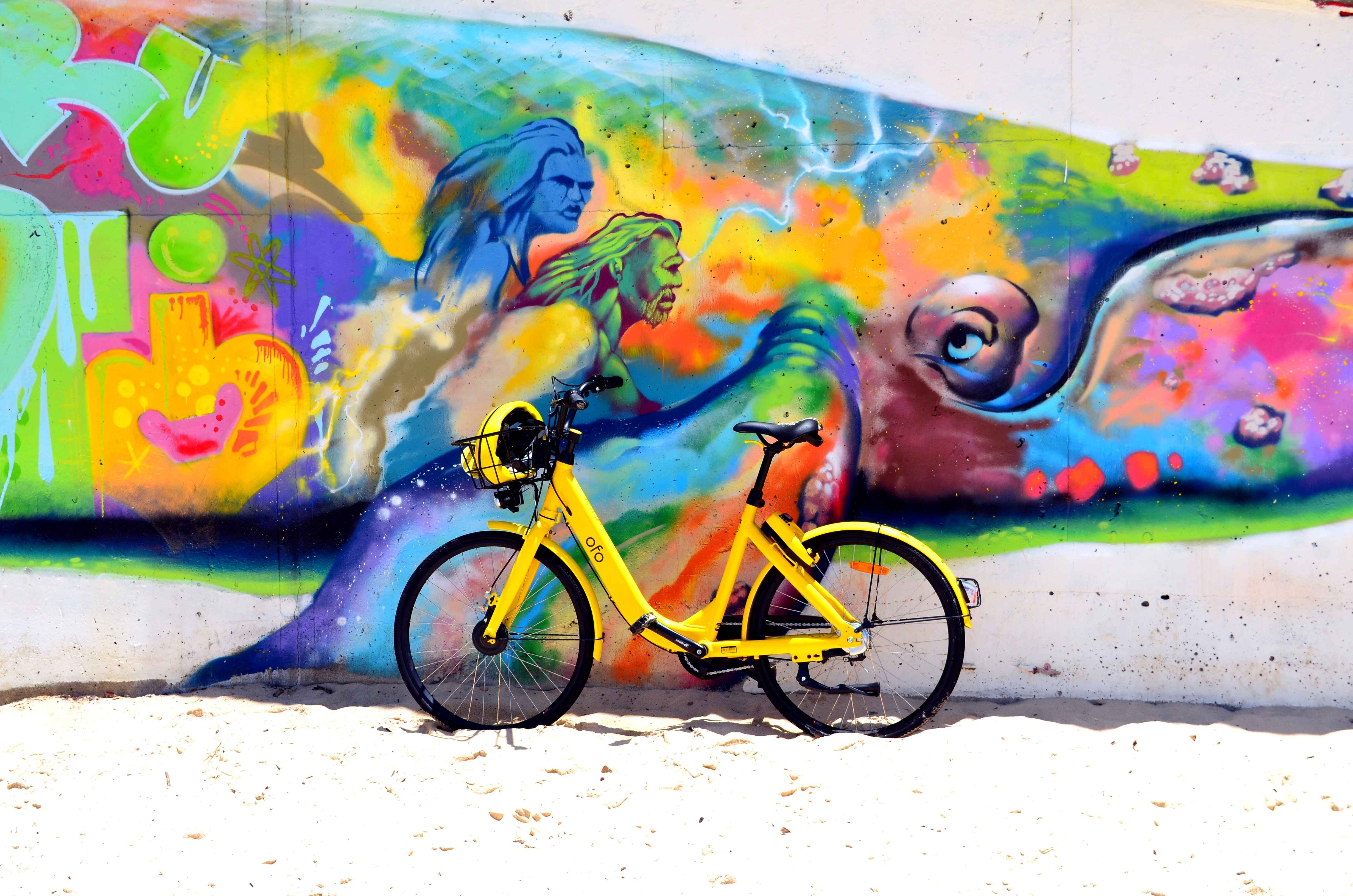 green bicycle park beside wall with human painting during daytime