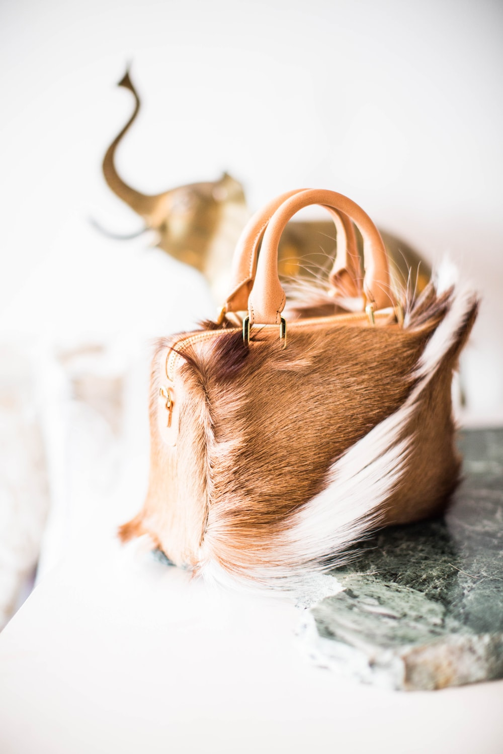 selective focus photography of brown and white leather handbag
