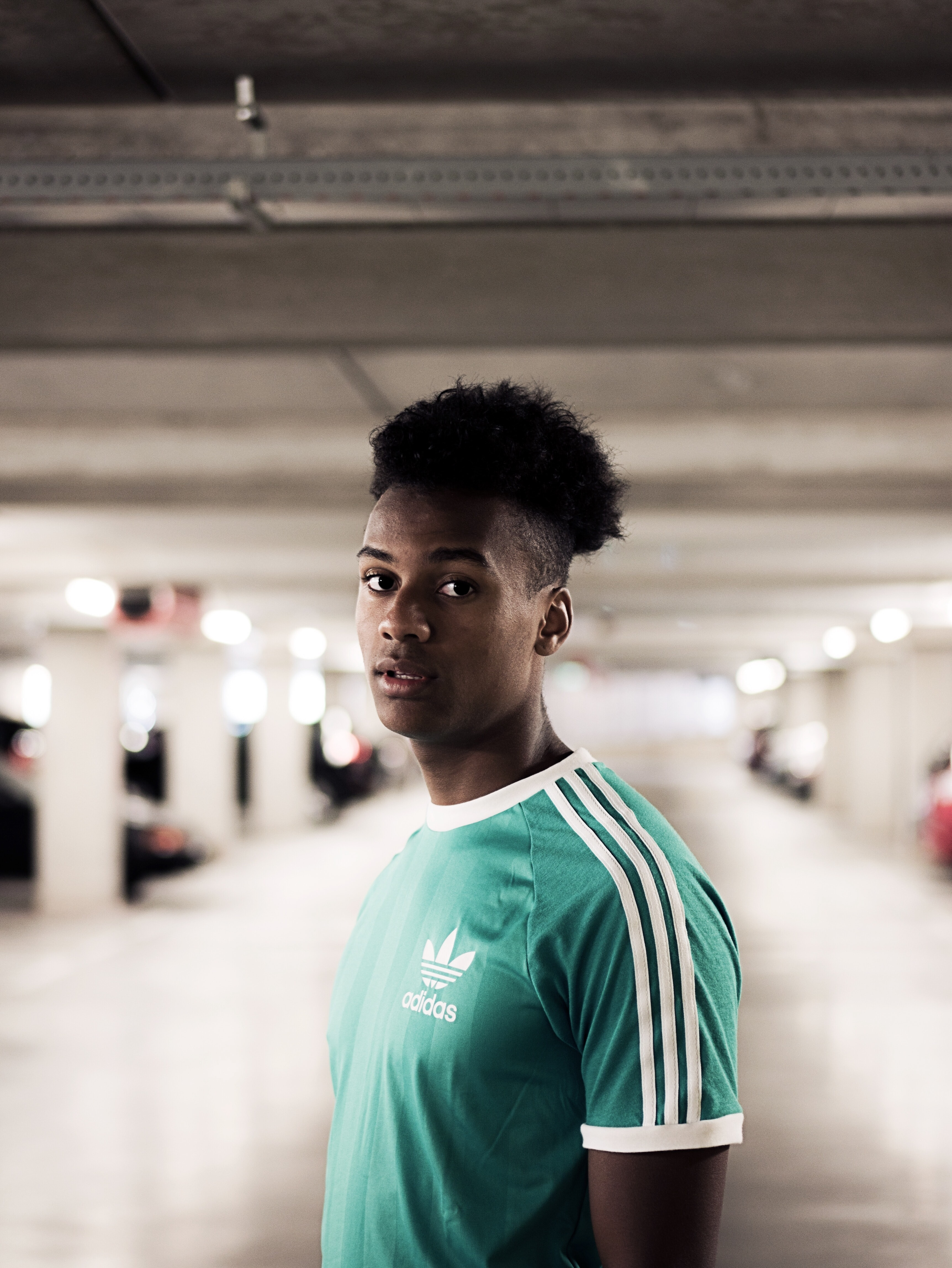 closeup photography of man in teal and white adidas crew-neck t-shirt