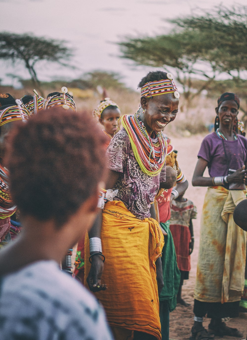 smiling woman dancing around people in tribe during daytime