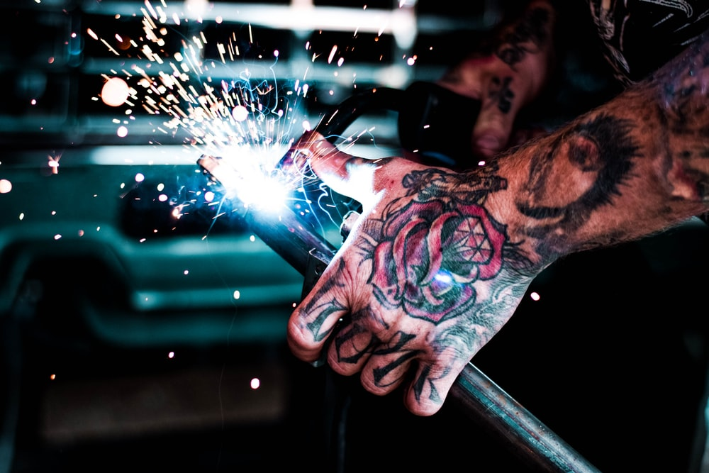 man welding metal rod