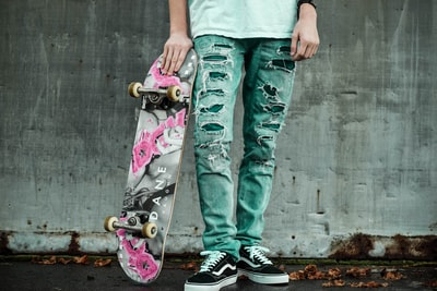 man standing next to wall holding gray and pink skateboard