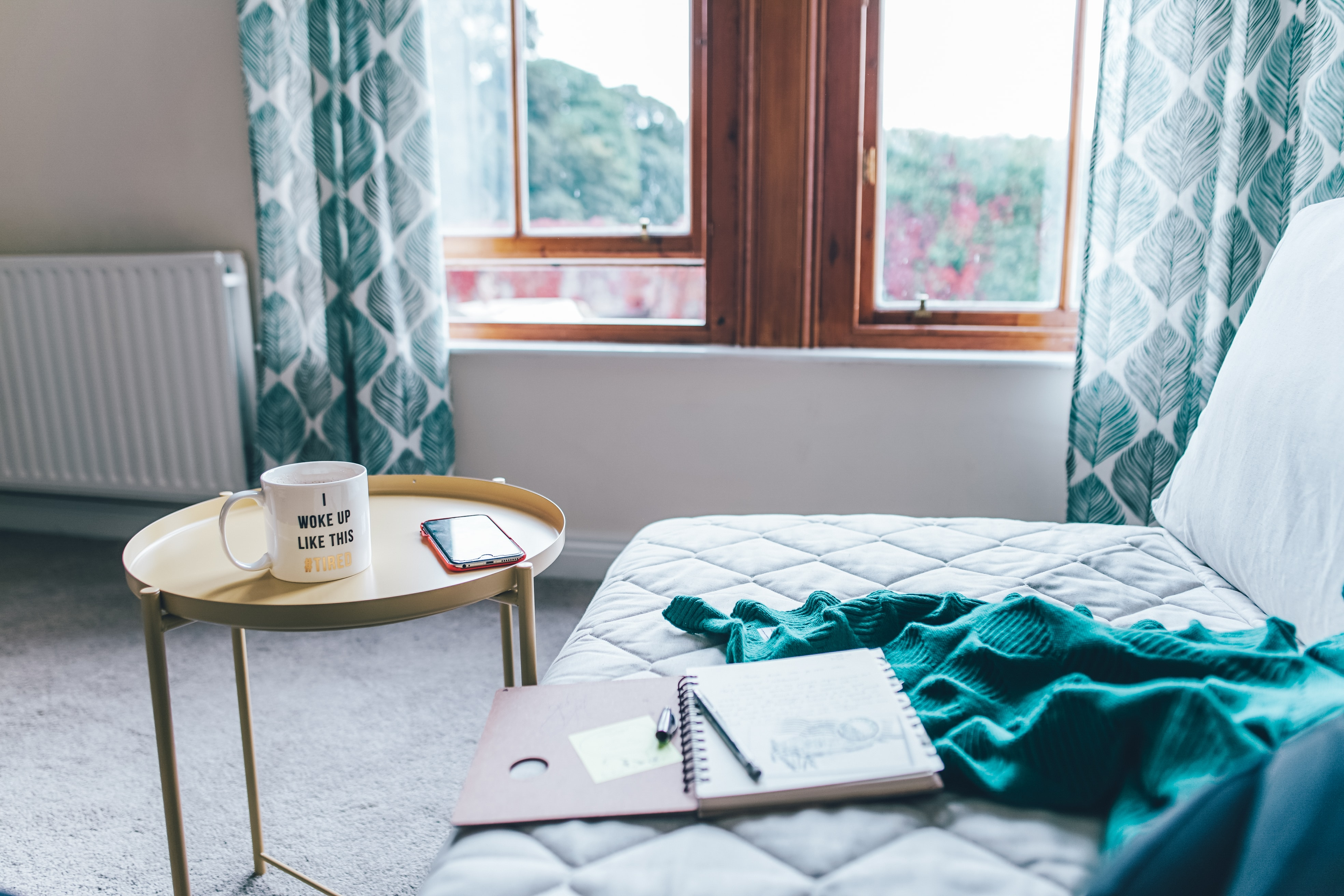 quilted white mattress with spiral notebook and green comforter beside round yellow end table inside room