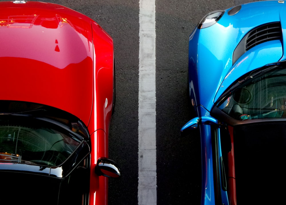 top view photo of red and blue convertibles on asphalt road