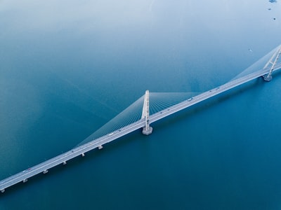 gray concrete bridge on body of water in aerial photography bridge teams background