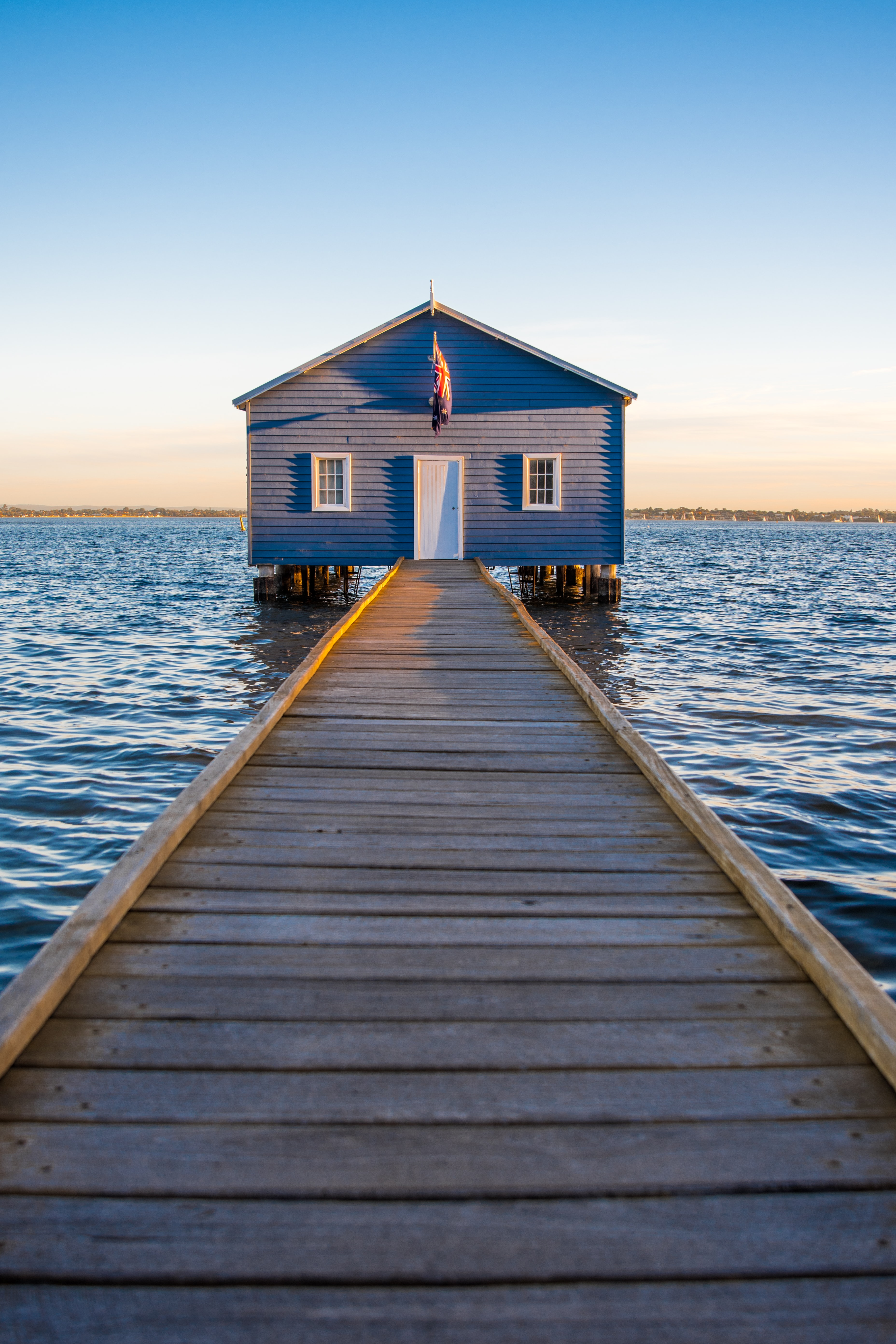 blue and white wooden house on sea under clear blue sky during daytime