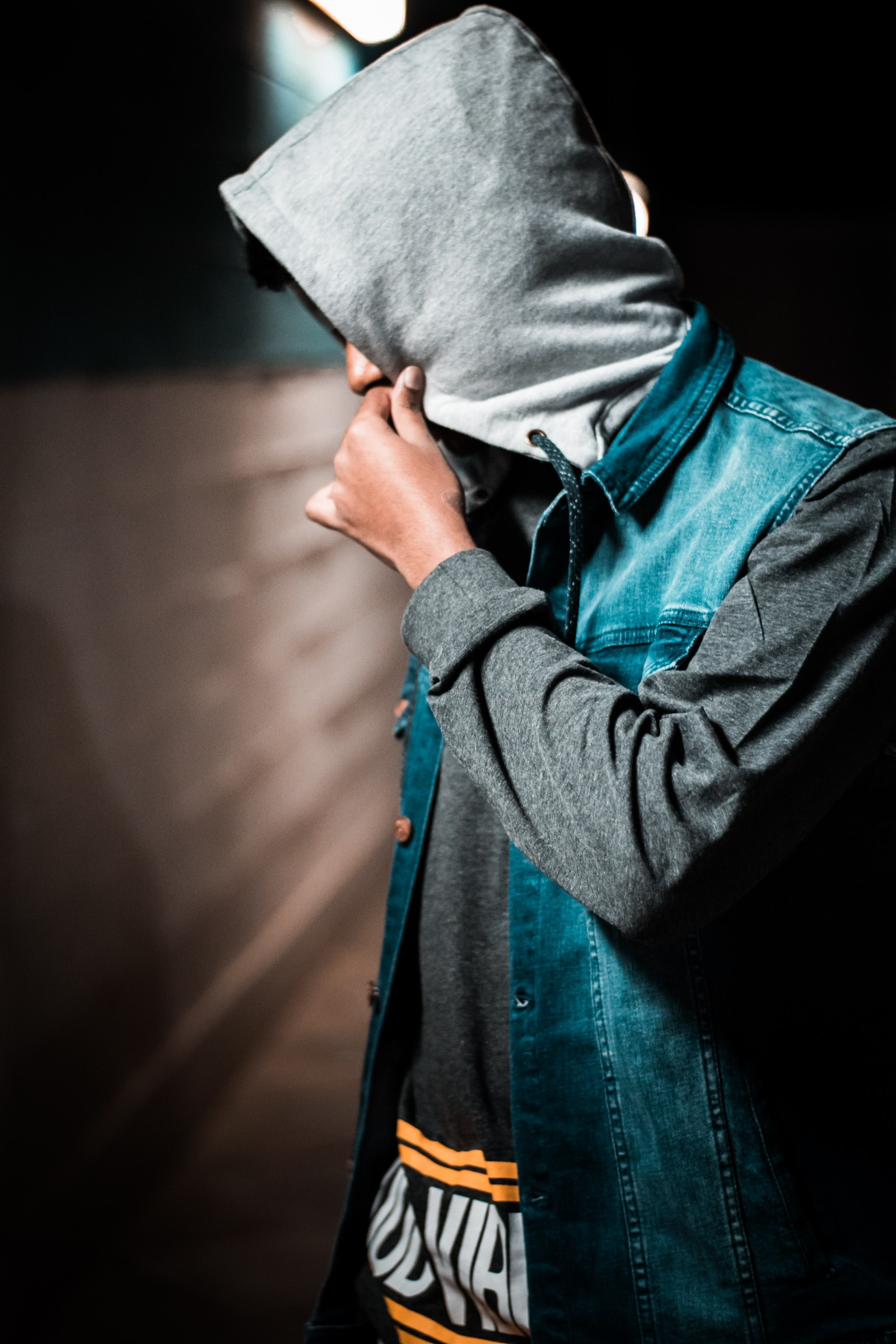man wearing denim jacket standing near wall