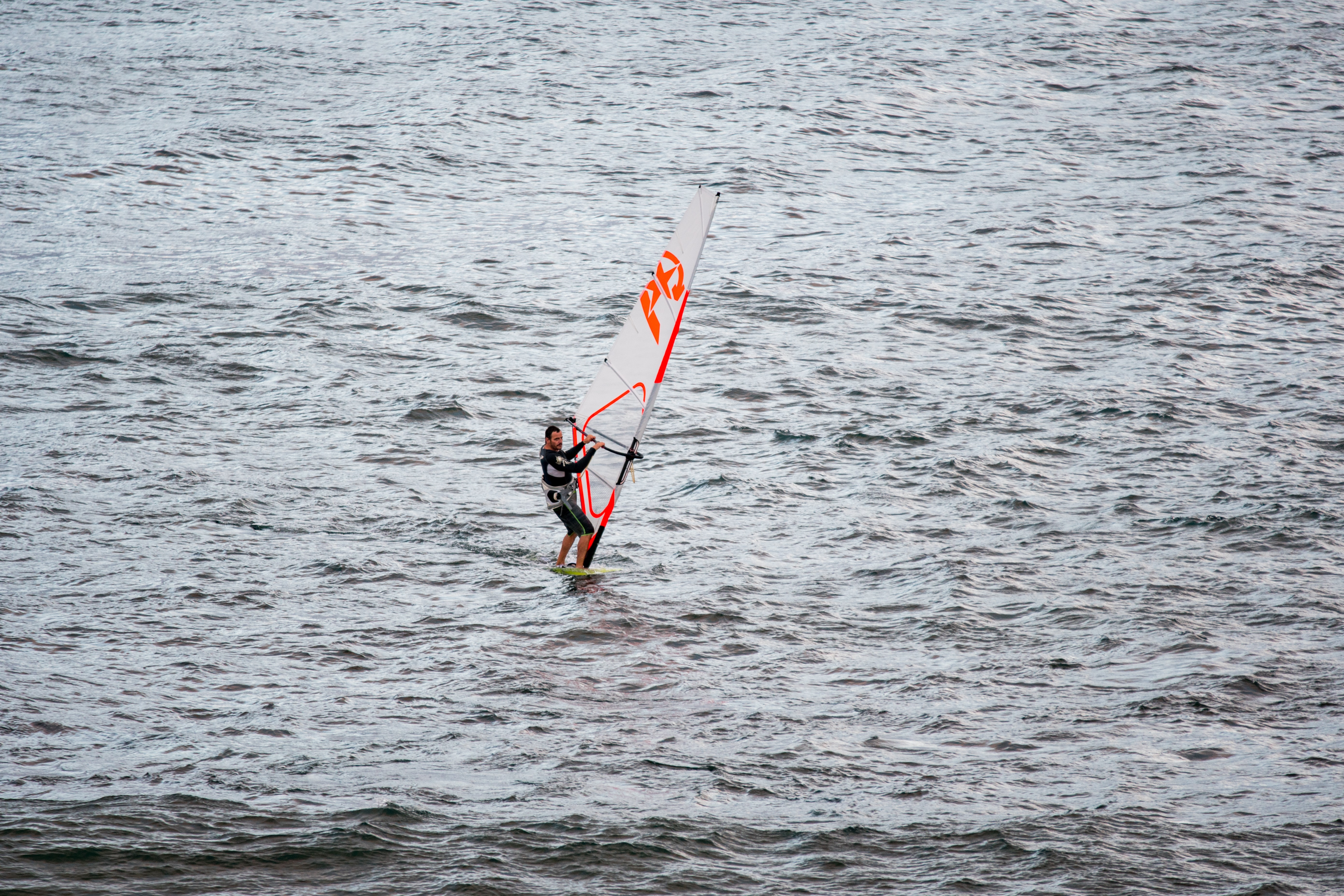 person riding windsurfing on body of water