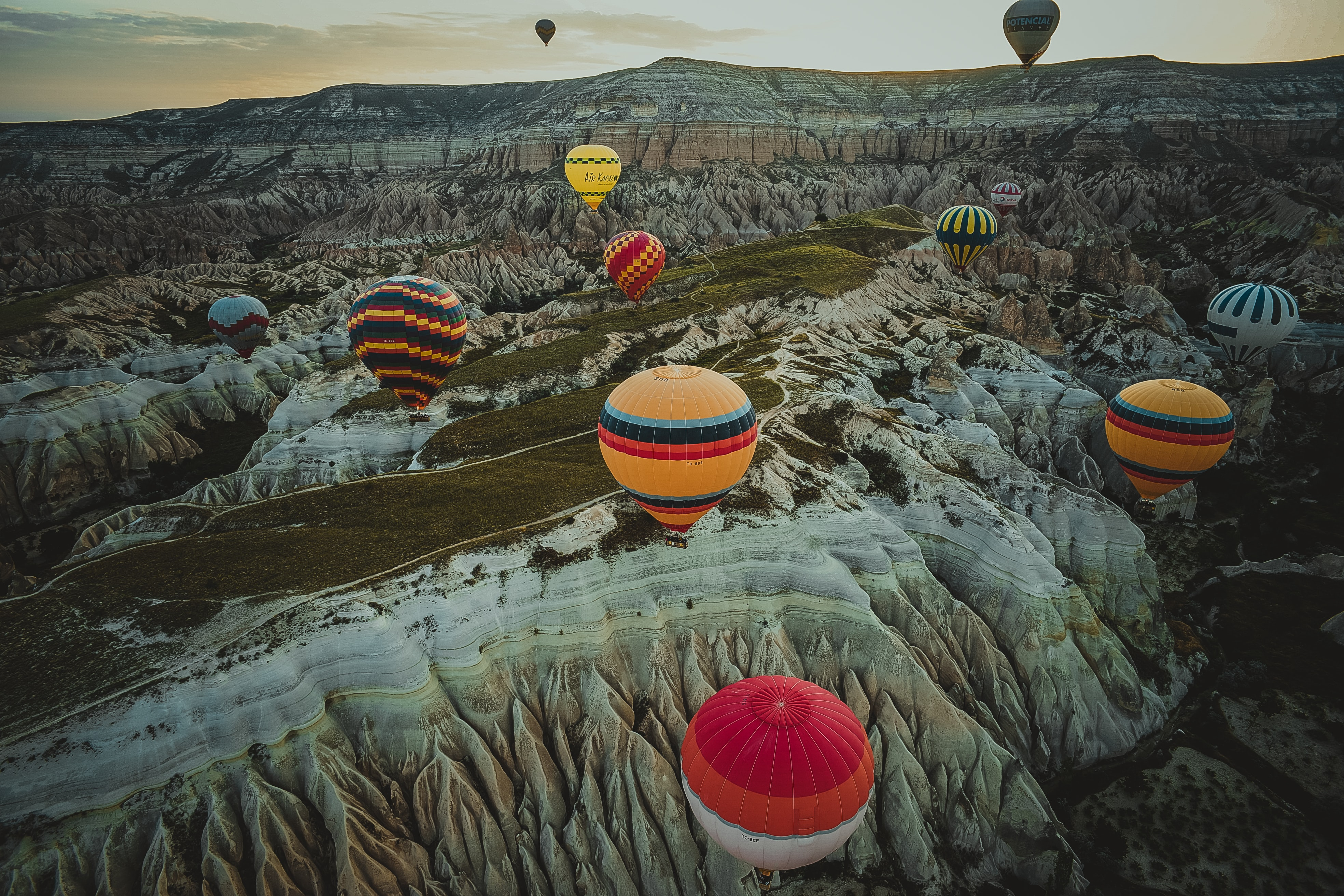 assorted-color hot air balloons flying above canyon