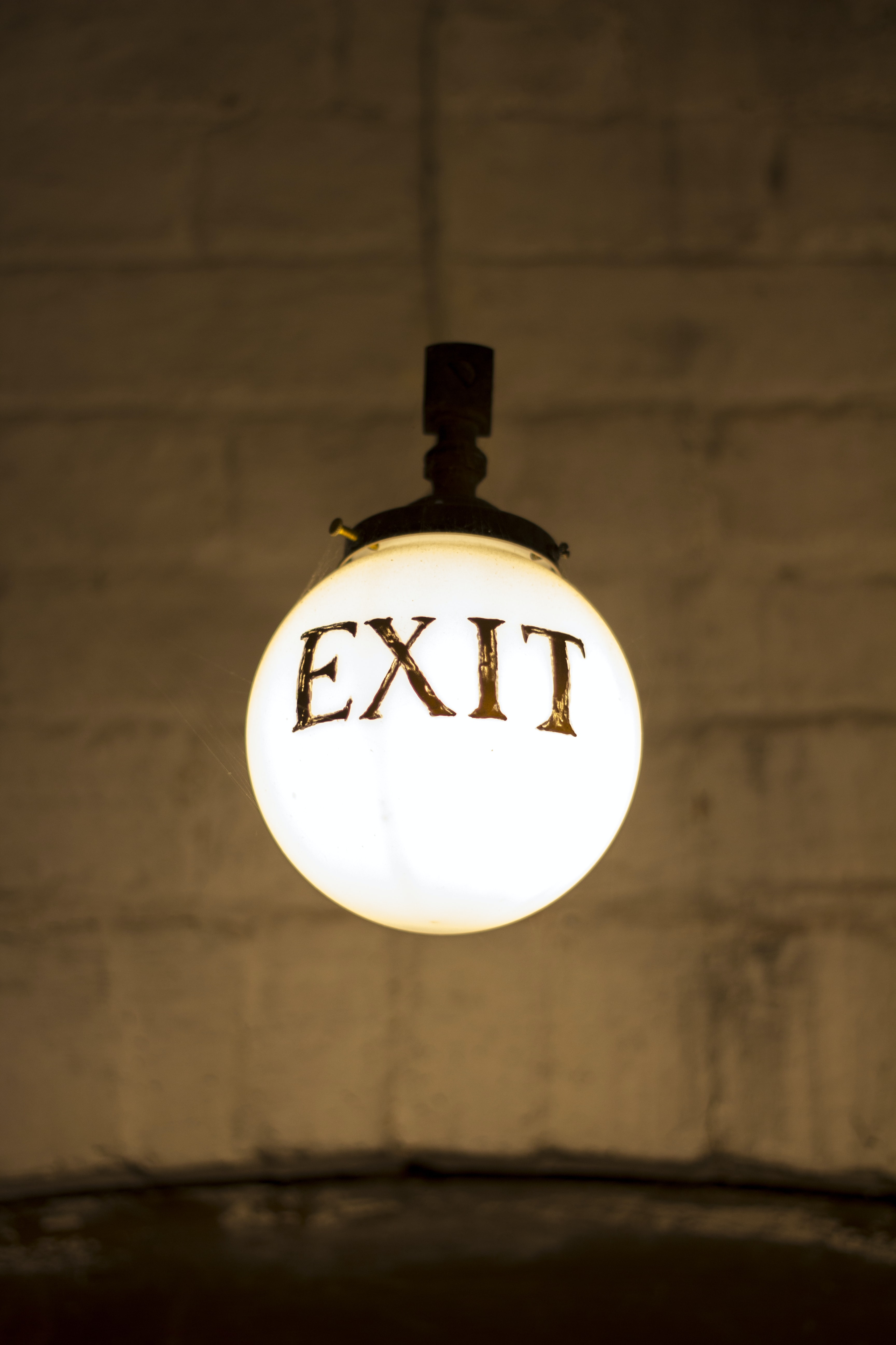 closeup photography of white hanging bulb light with exit signage