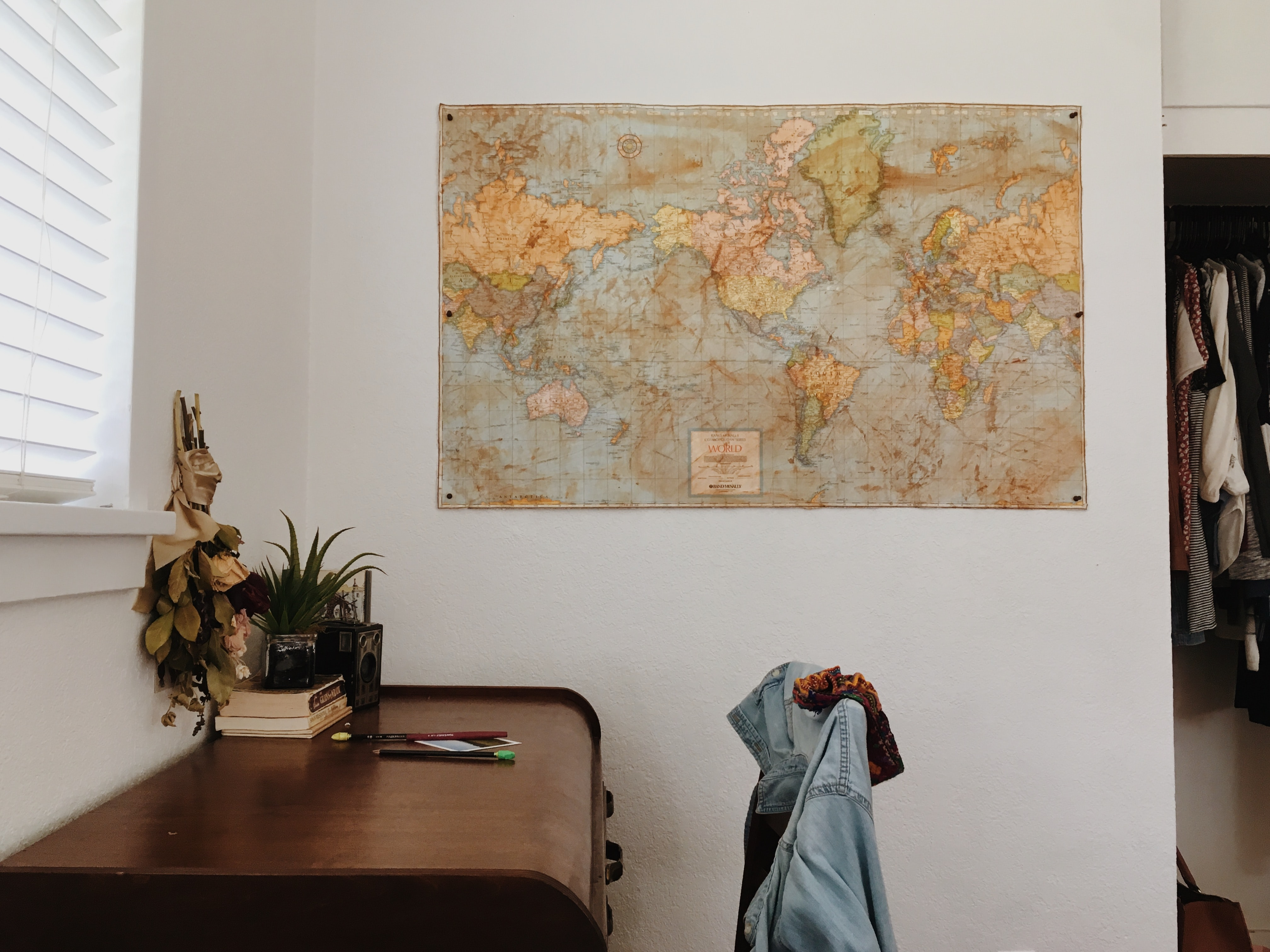 world map placing on wall near brown wooden desk