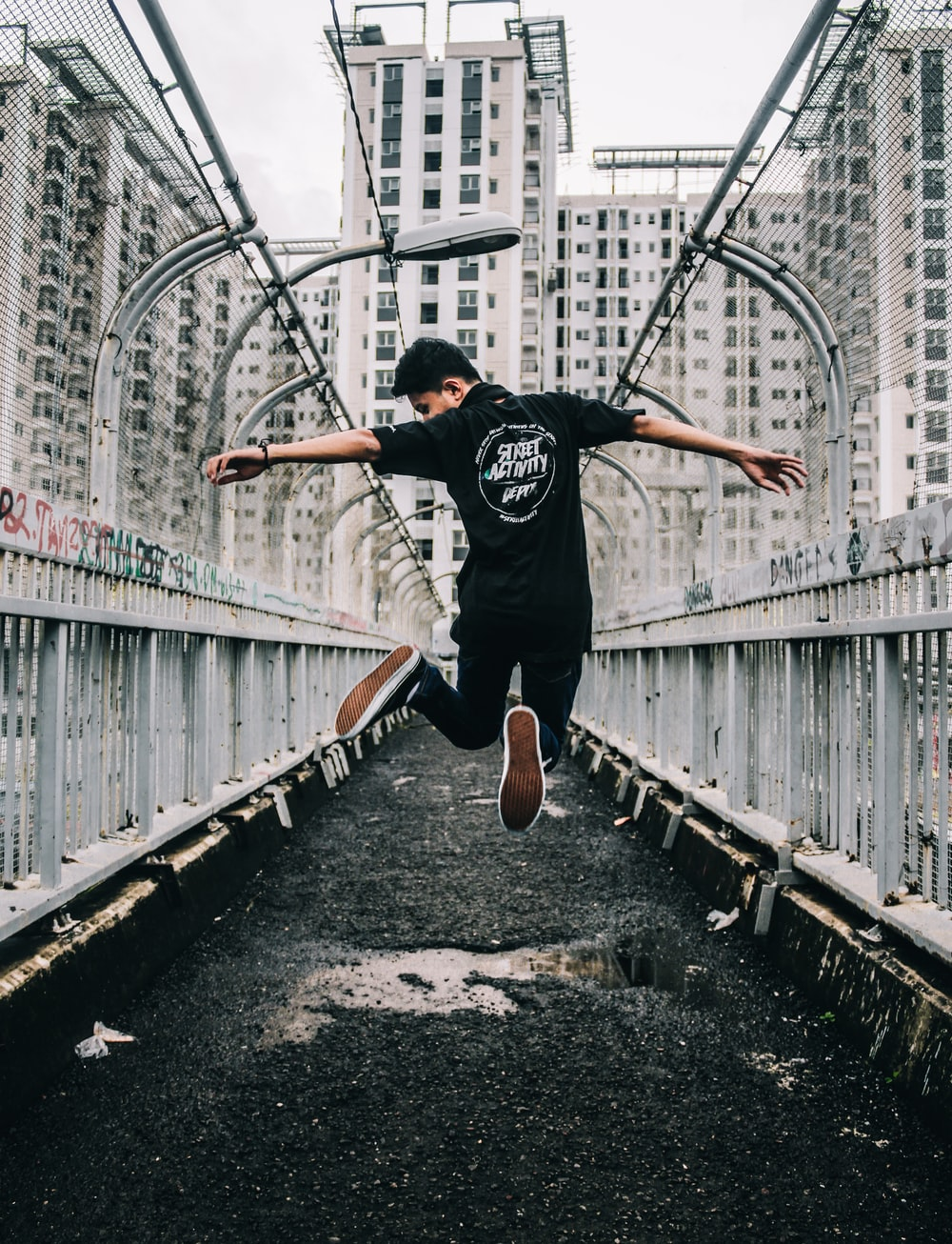 man jumping on pathway surrounded by buildings during daytime