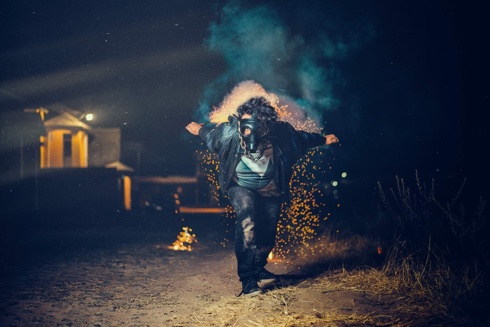 low-light photo of man wearing gas mask bong about to run in between of green grass