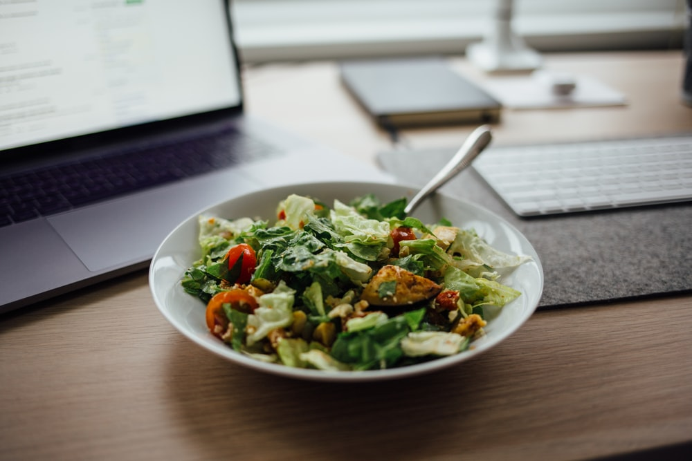 salad on white ceramic bowl on top of table near laptop