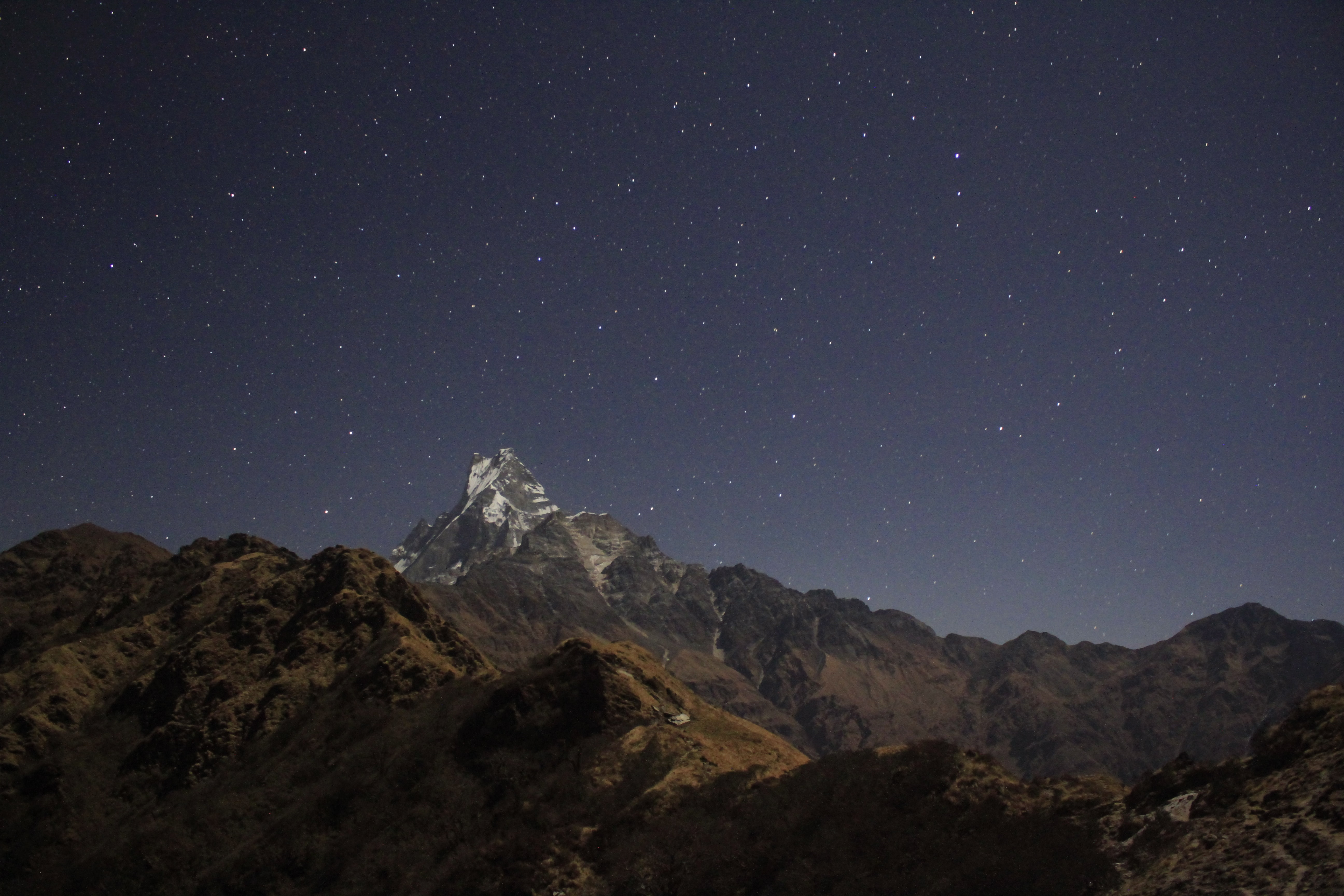 landscape photo of stars above brown mountain ridge