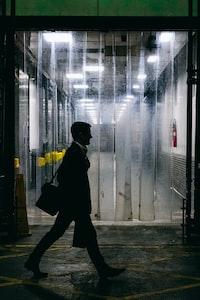 man walking in front of car wash garage