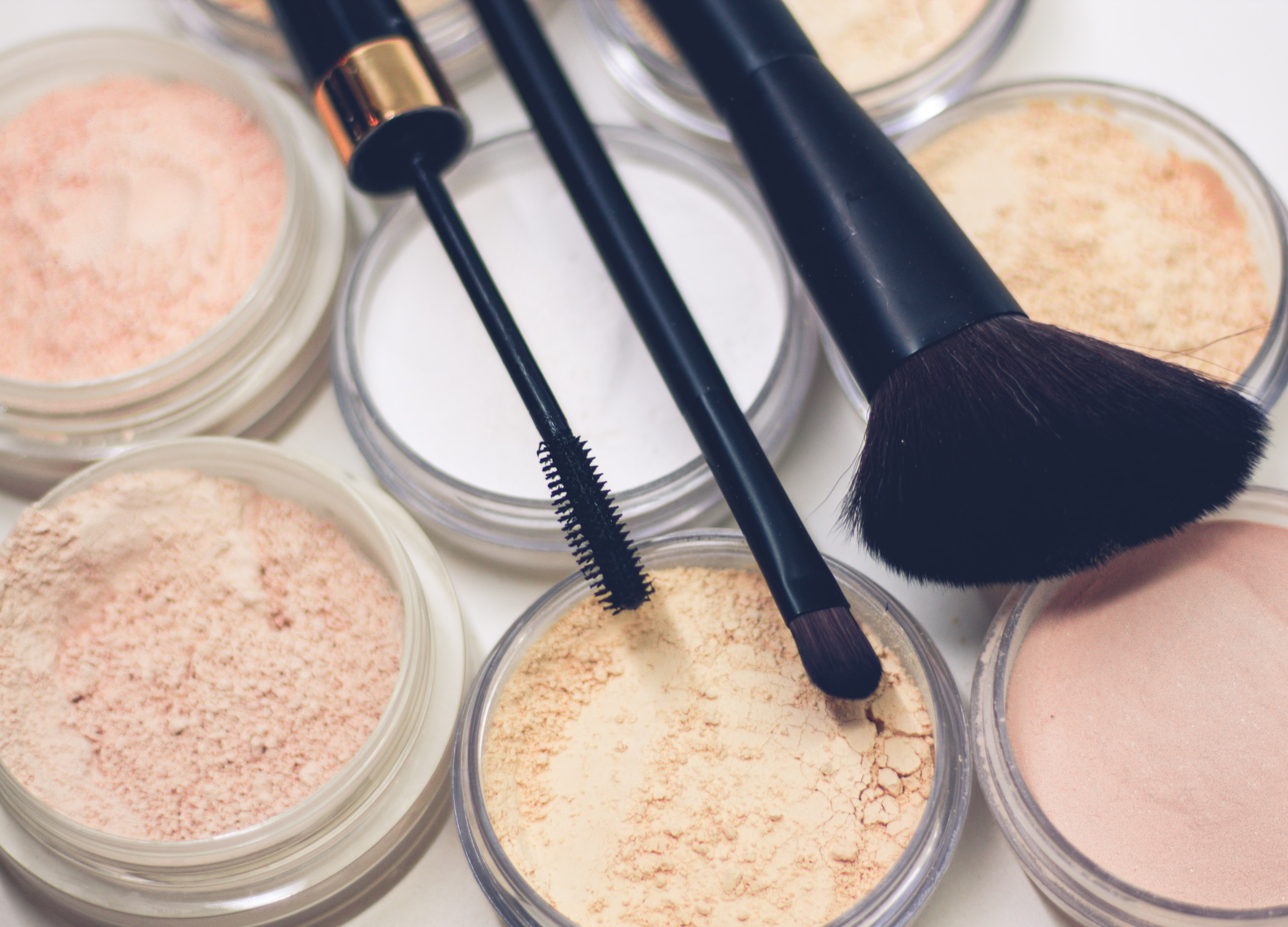 three makeup brushes on top of compact powders