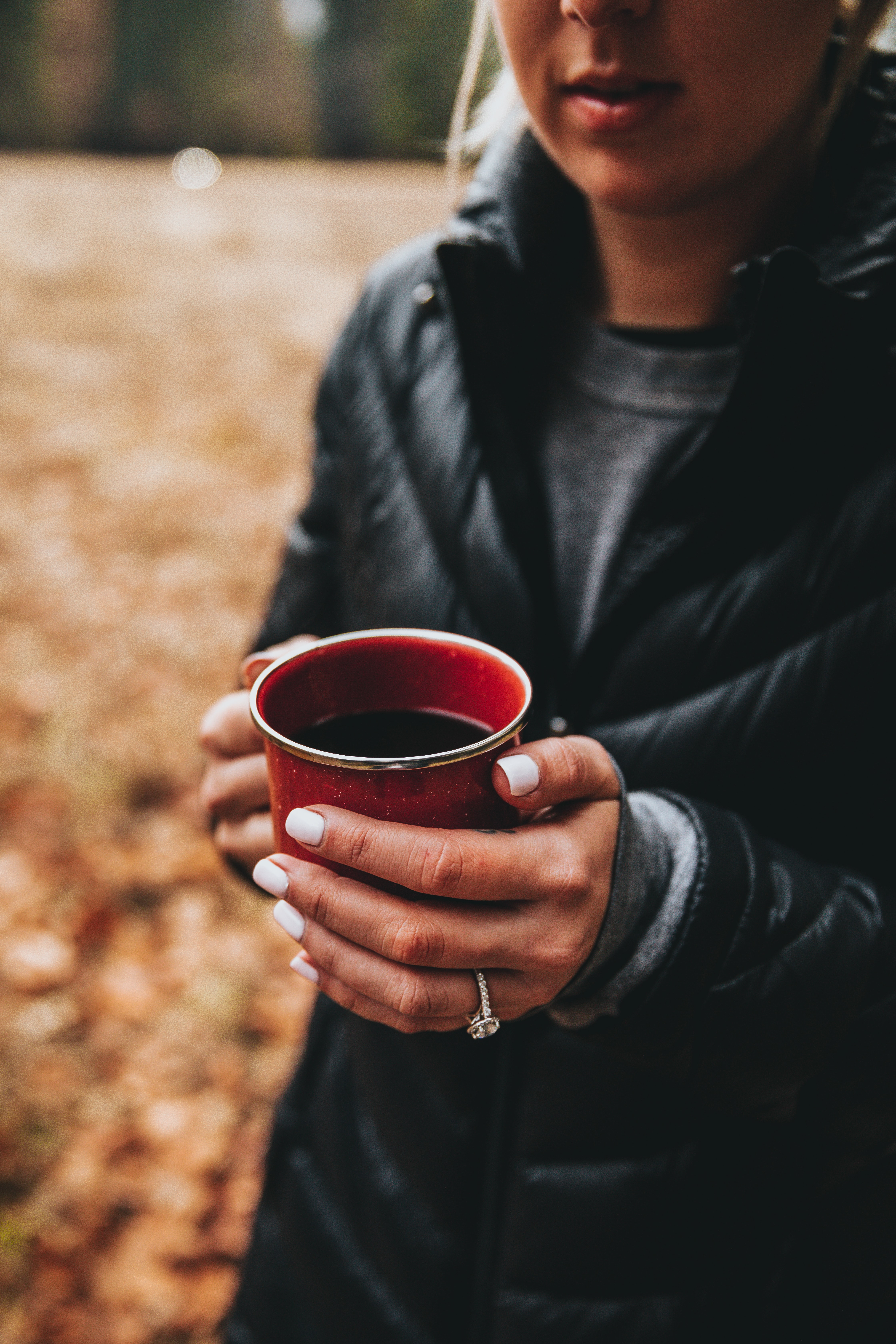 woman holding black liquid-filled red cup selective focus photo