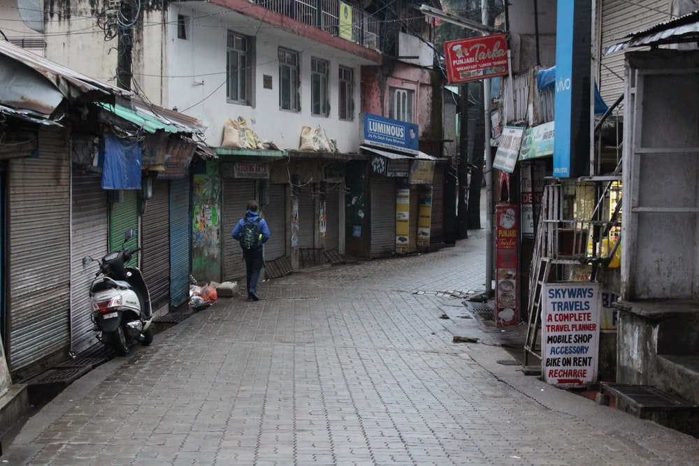 person in blue hoodie walking on street surrounded by buildings