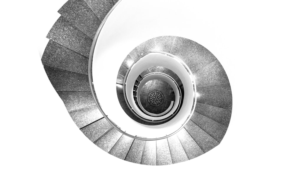 grayscale photography of spiral stairs with no people