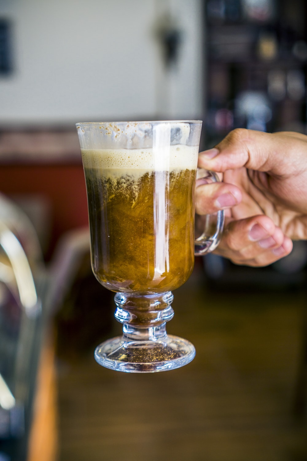 person holding glass mug with brown liquid