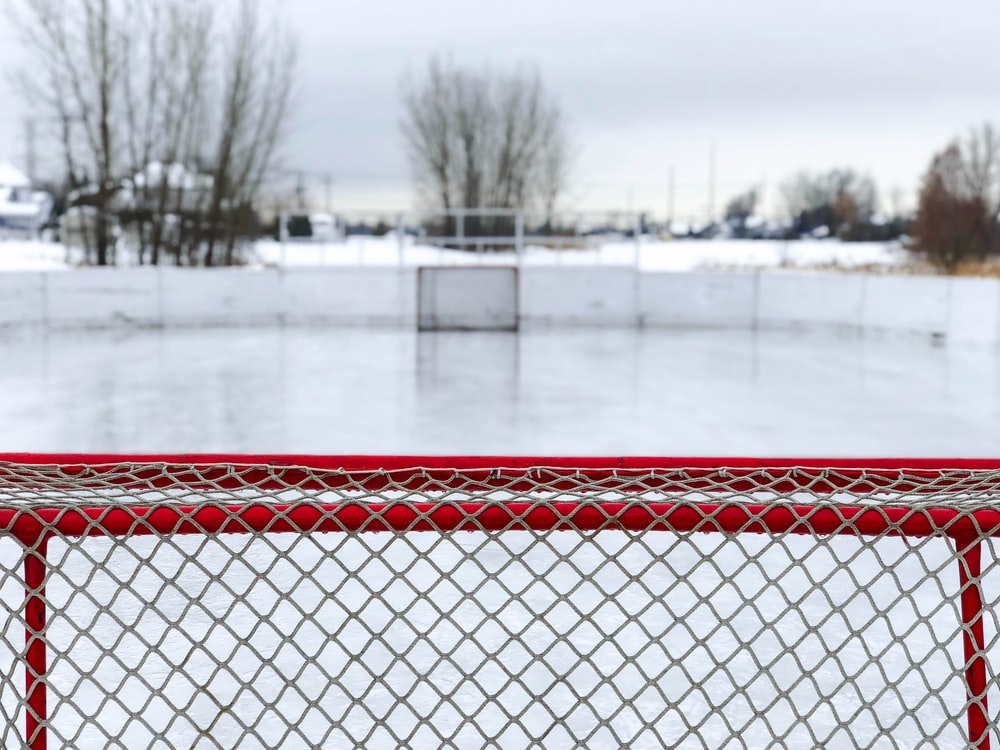 red and white goal net on ice field