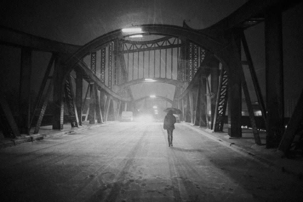 grayscale photo of woman under umbrella walking on suspension bridge