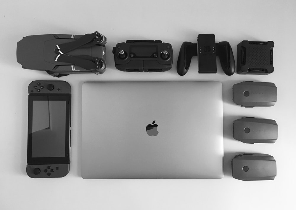 MacBook Pro near black Nintendo Switch, and game controller set