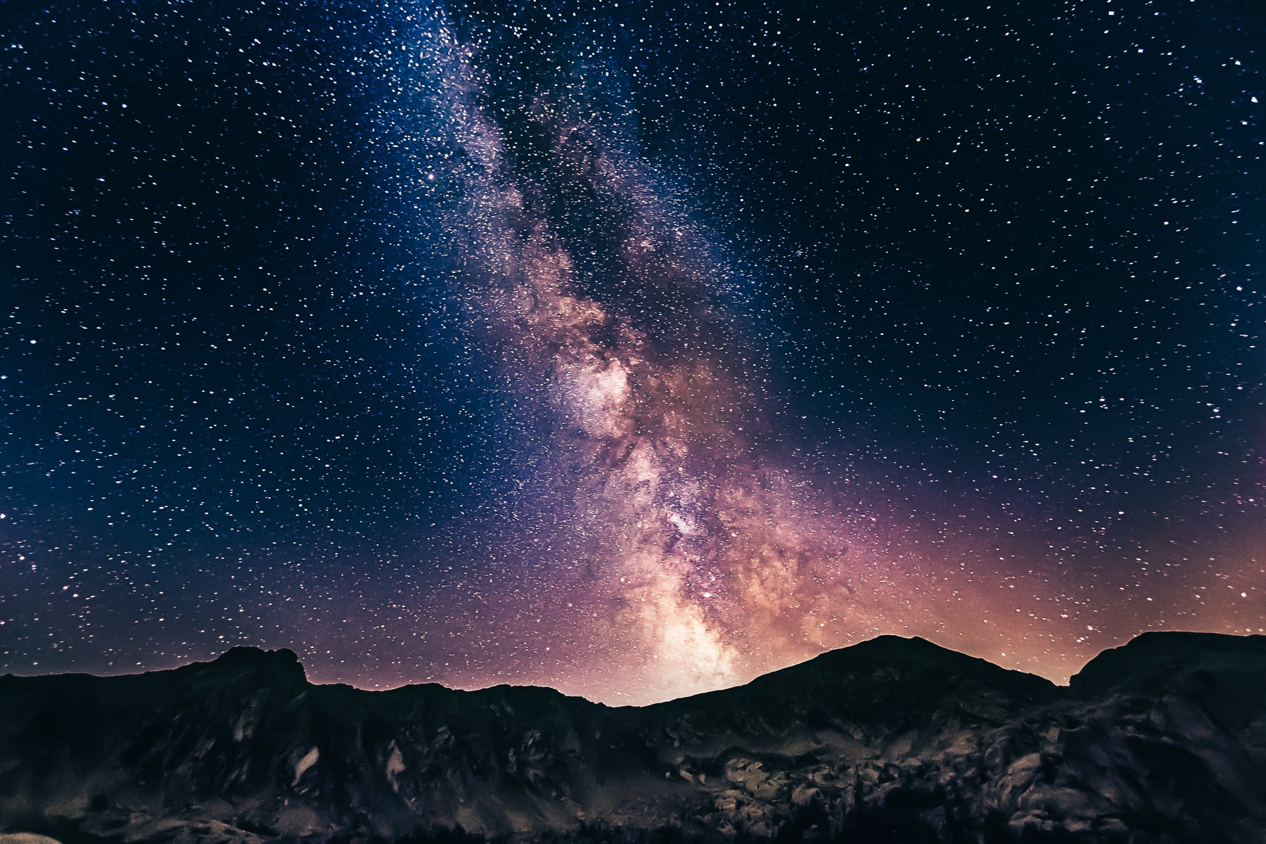 silhouette of mountains in front of stars