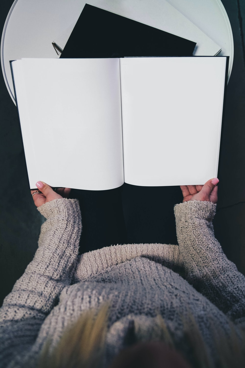 woman wearing sweater opening blank book
