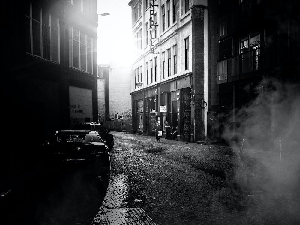 grayscale photo of road between buildings