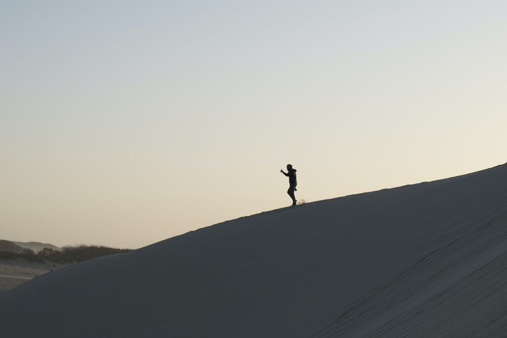 person standing on sand under white sky during daytime