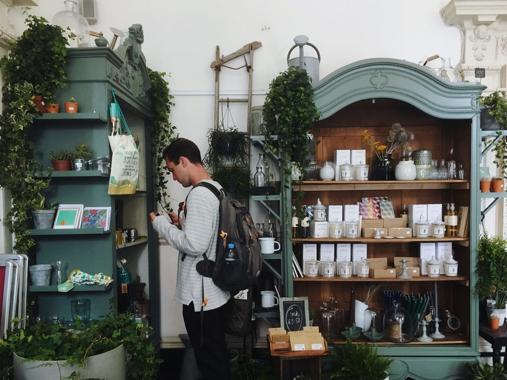 man in grey sweatshirt and brown backpack standing beside green wooden shelf