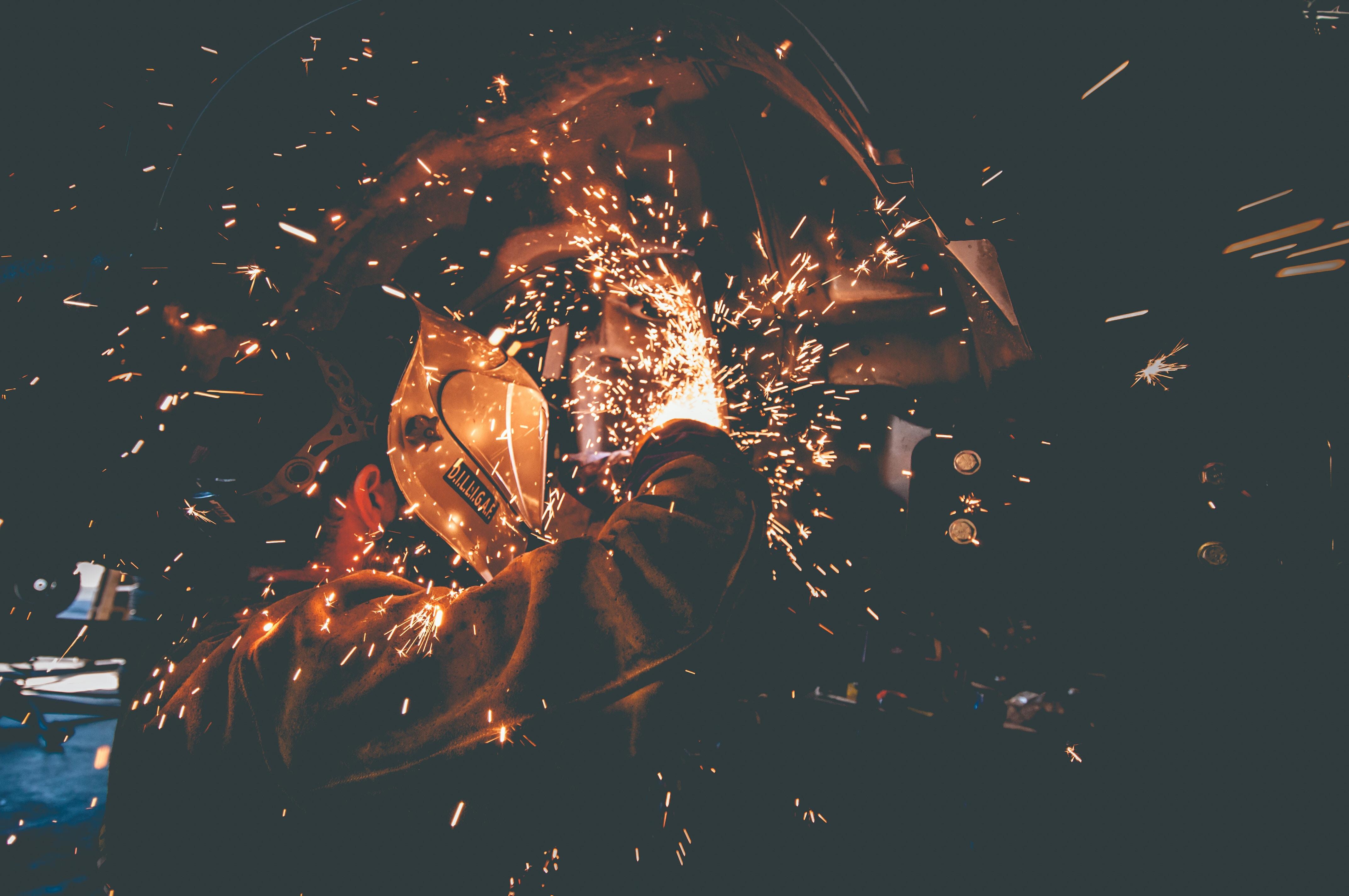 man wearing welding mask grinding metal