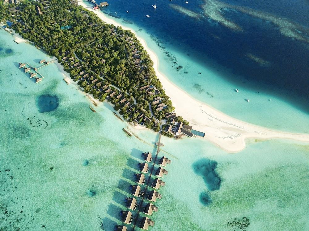 aerial shot of nipa huts on body of water near island