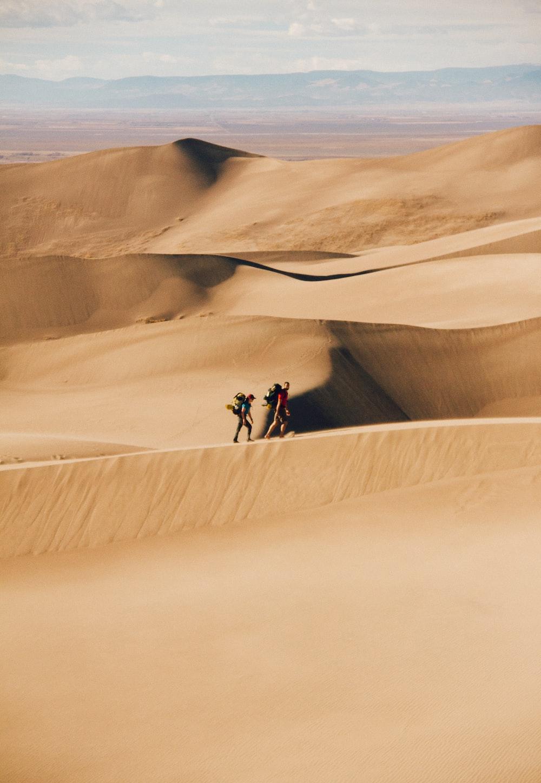 people walking in the desert during daytime