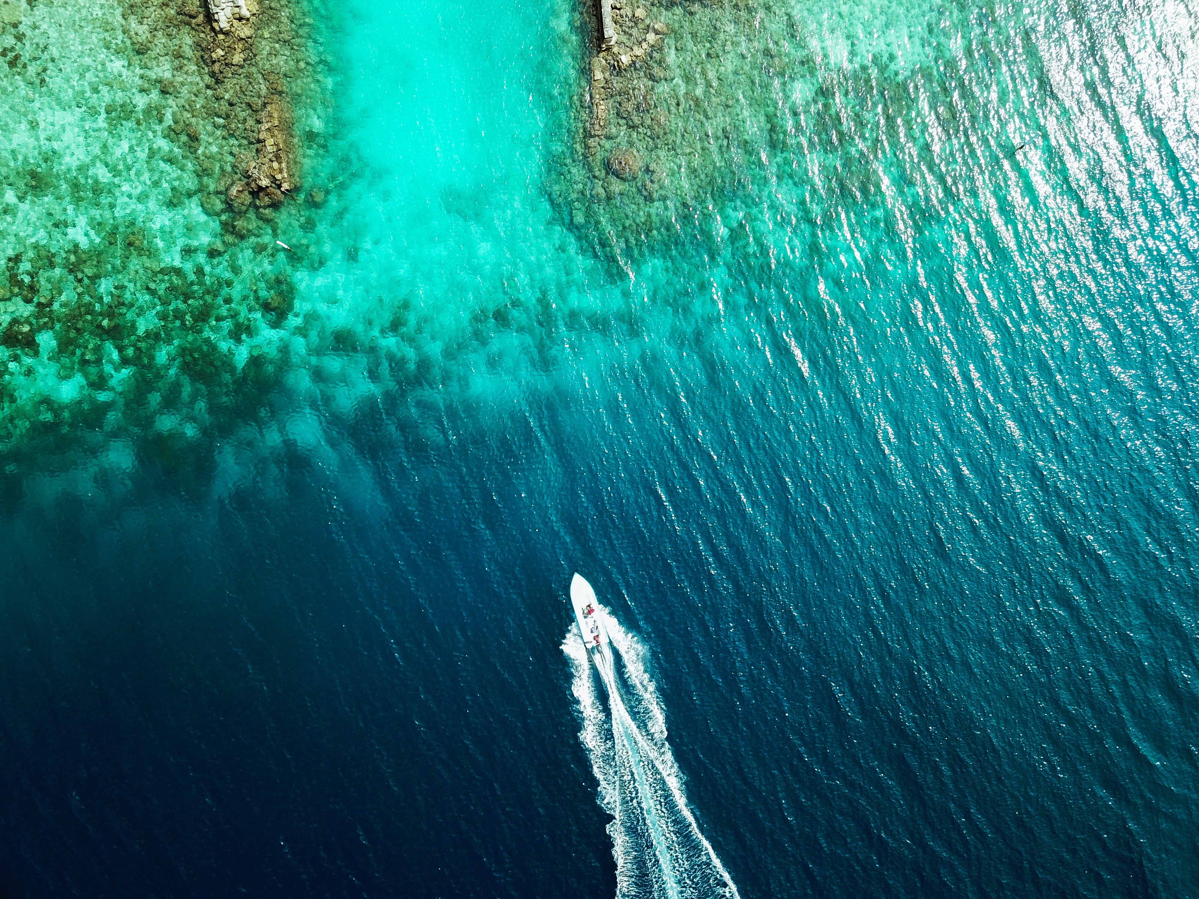 aerial view of boat sailing through island