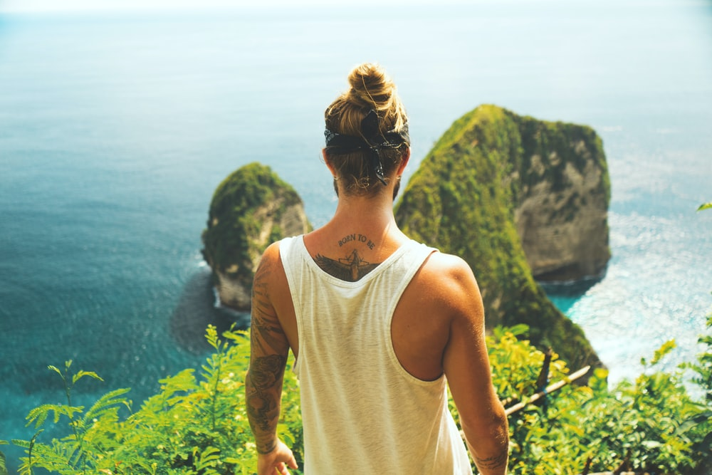 man in white tank top facing near the cliff