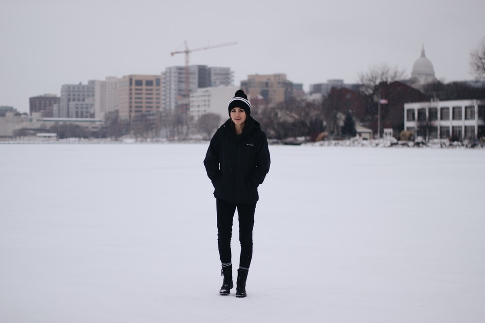 woman walking on field with snow and bulidings