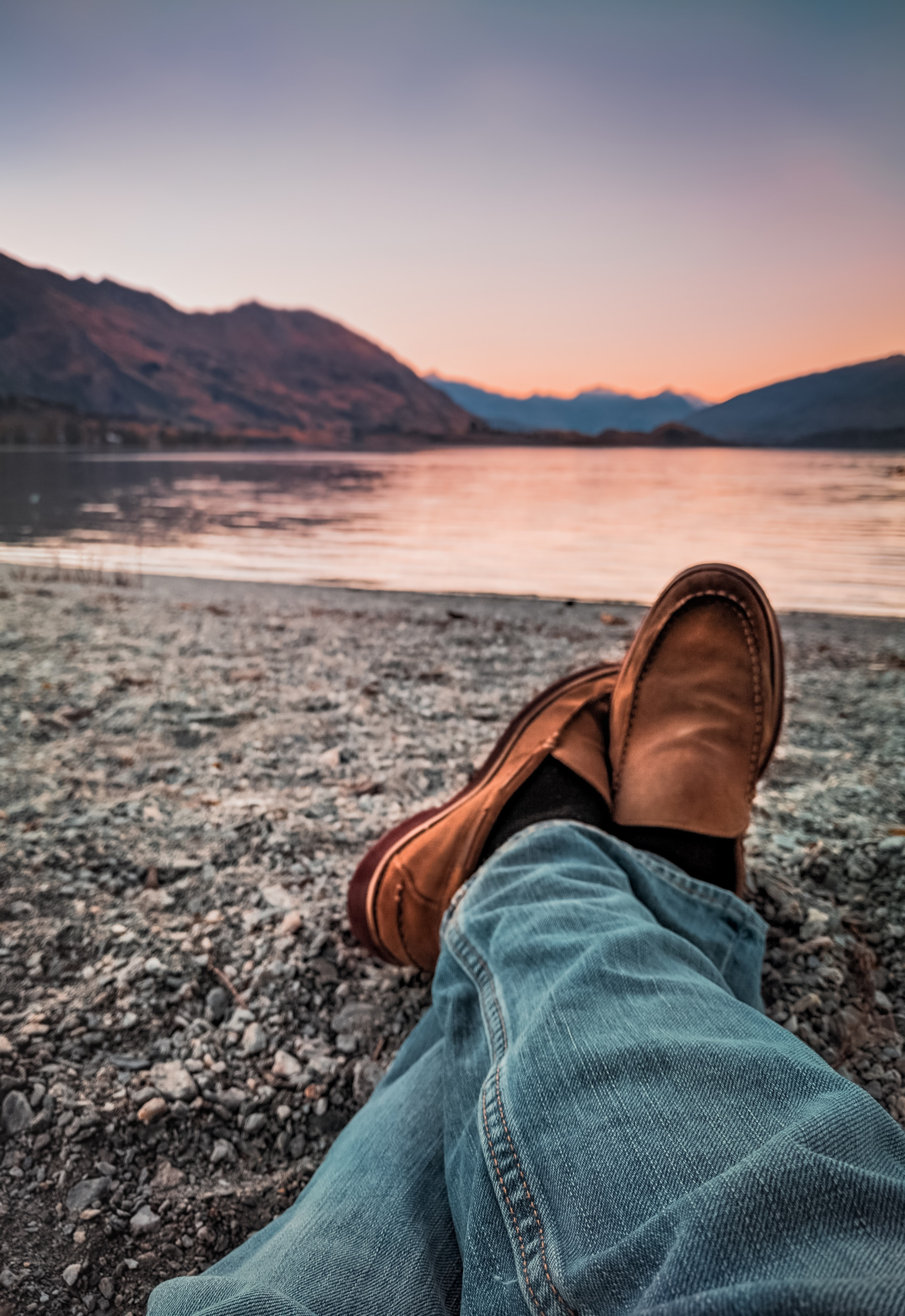 person wearing brown loafers sitting beside body of water