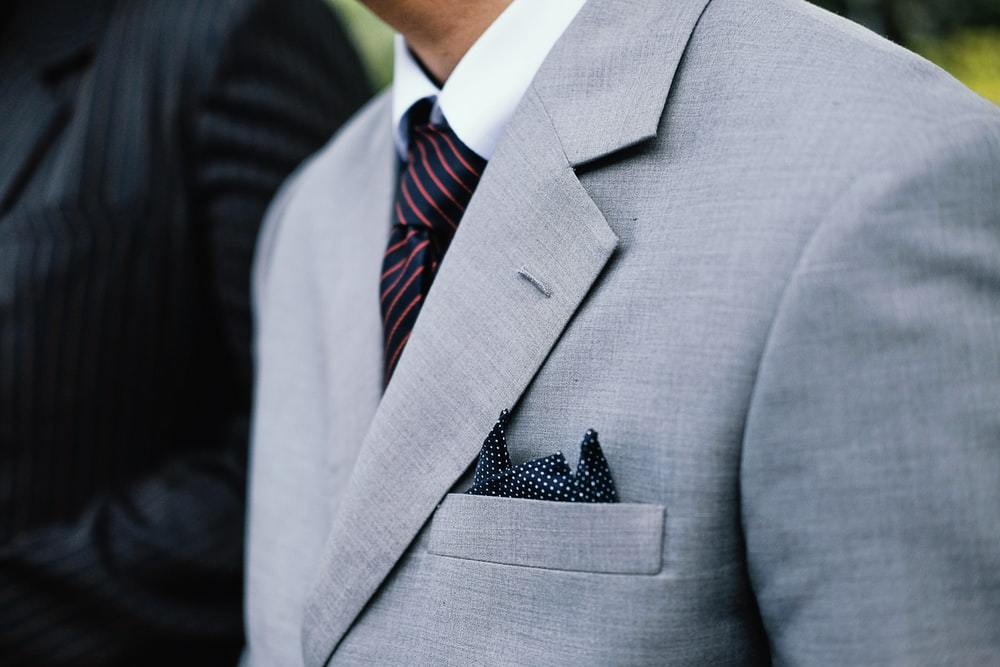 man wearing gray notched lapel suit jacket standing