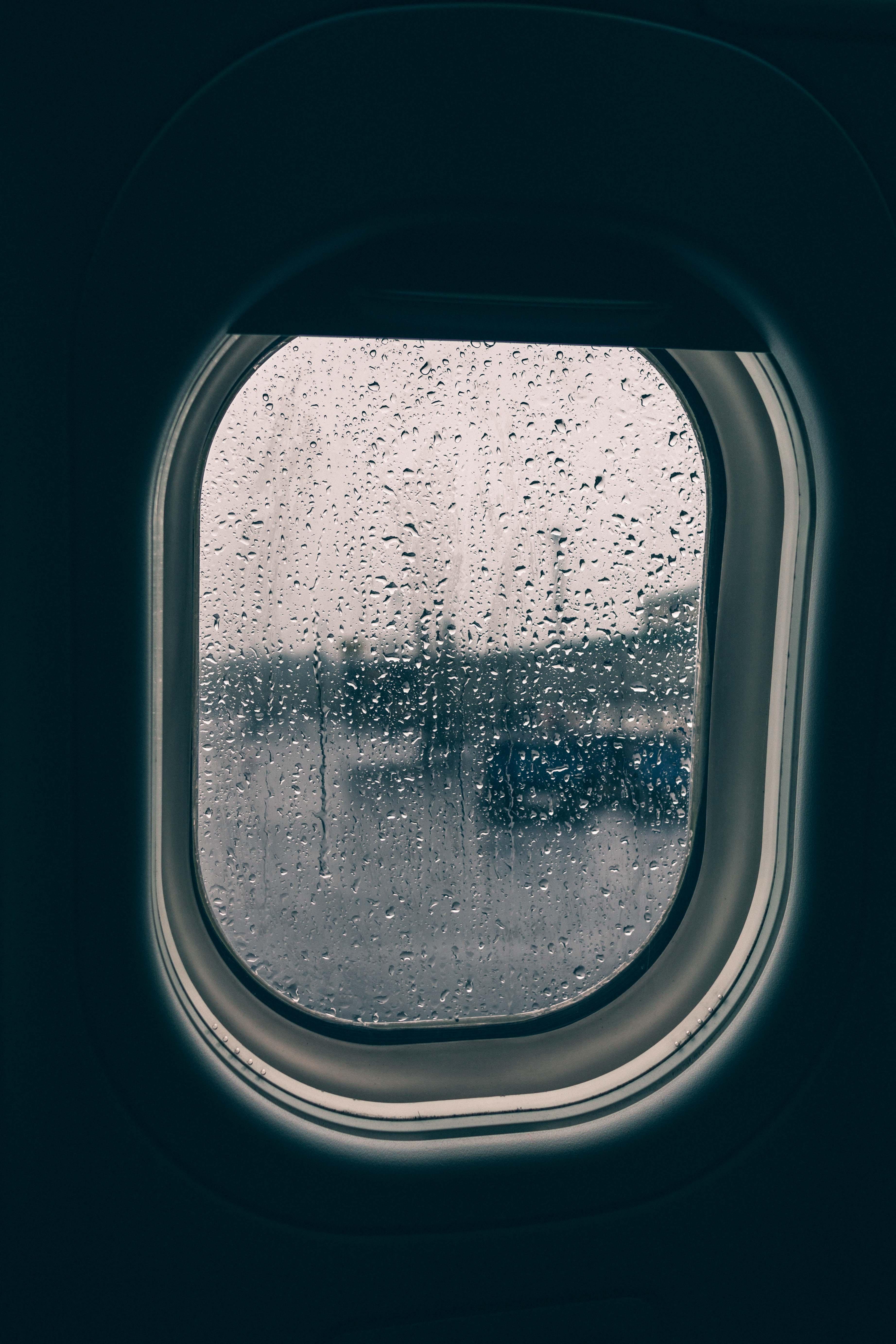 clear glass plane window full of rain droplets