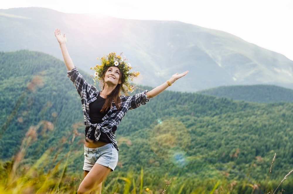 woman raising hands behind mountain covered by trees