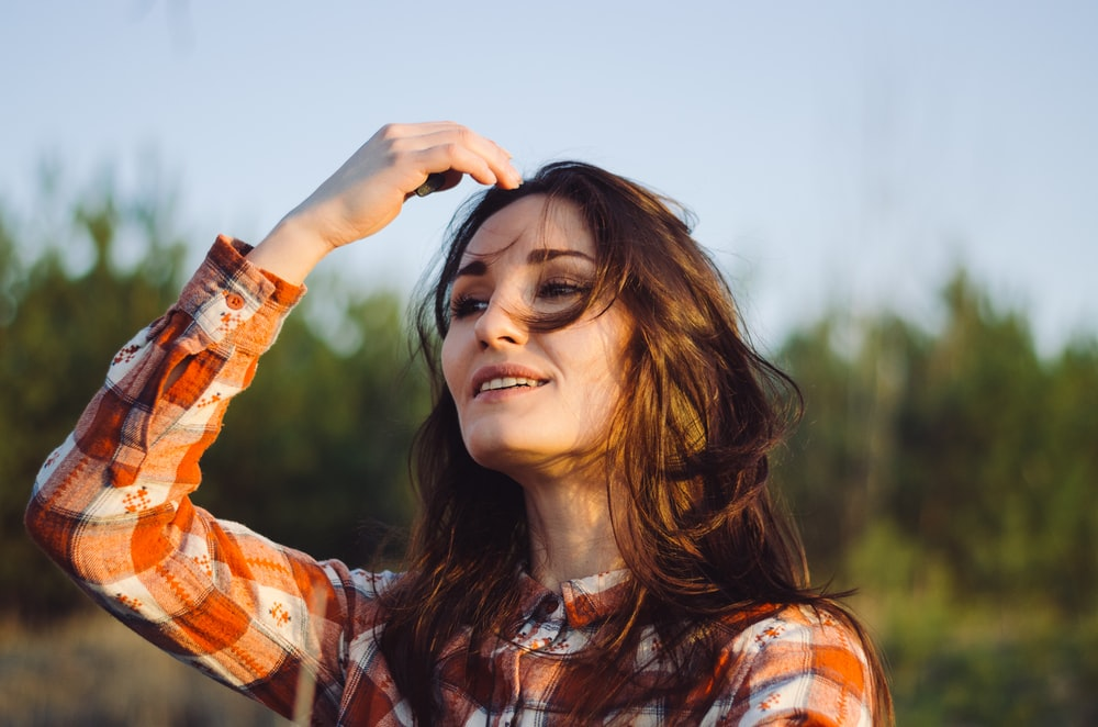 selective focus photography of woman touching her head