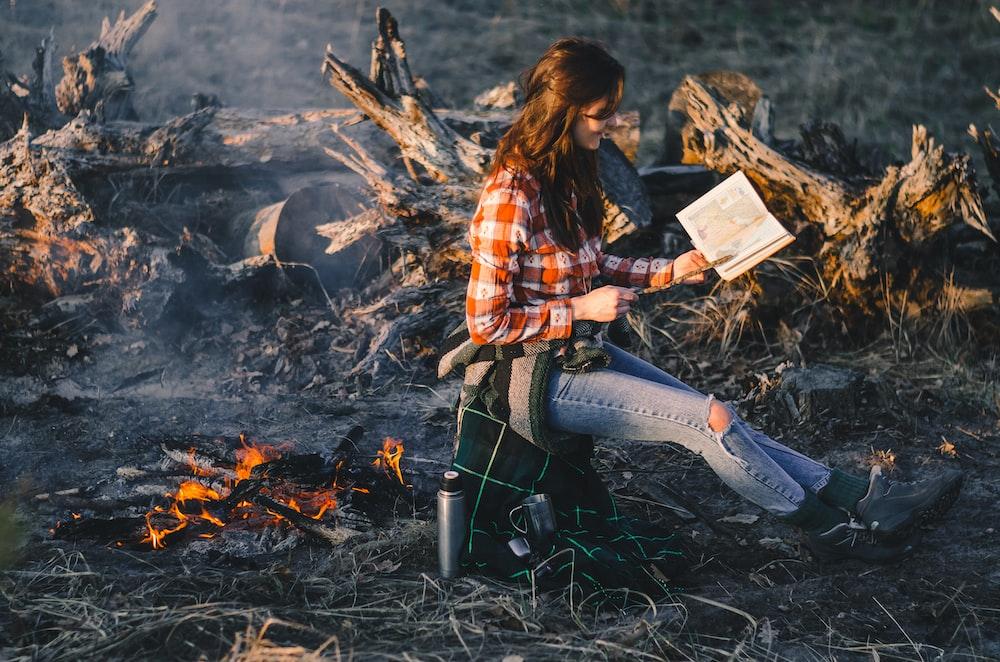 woman sitting while reading near bonfire