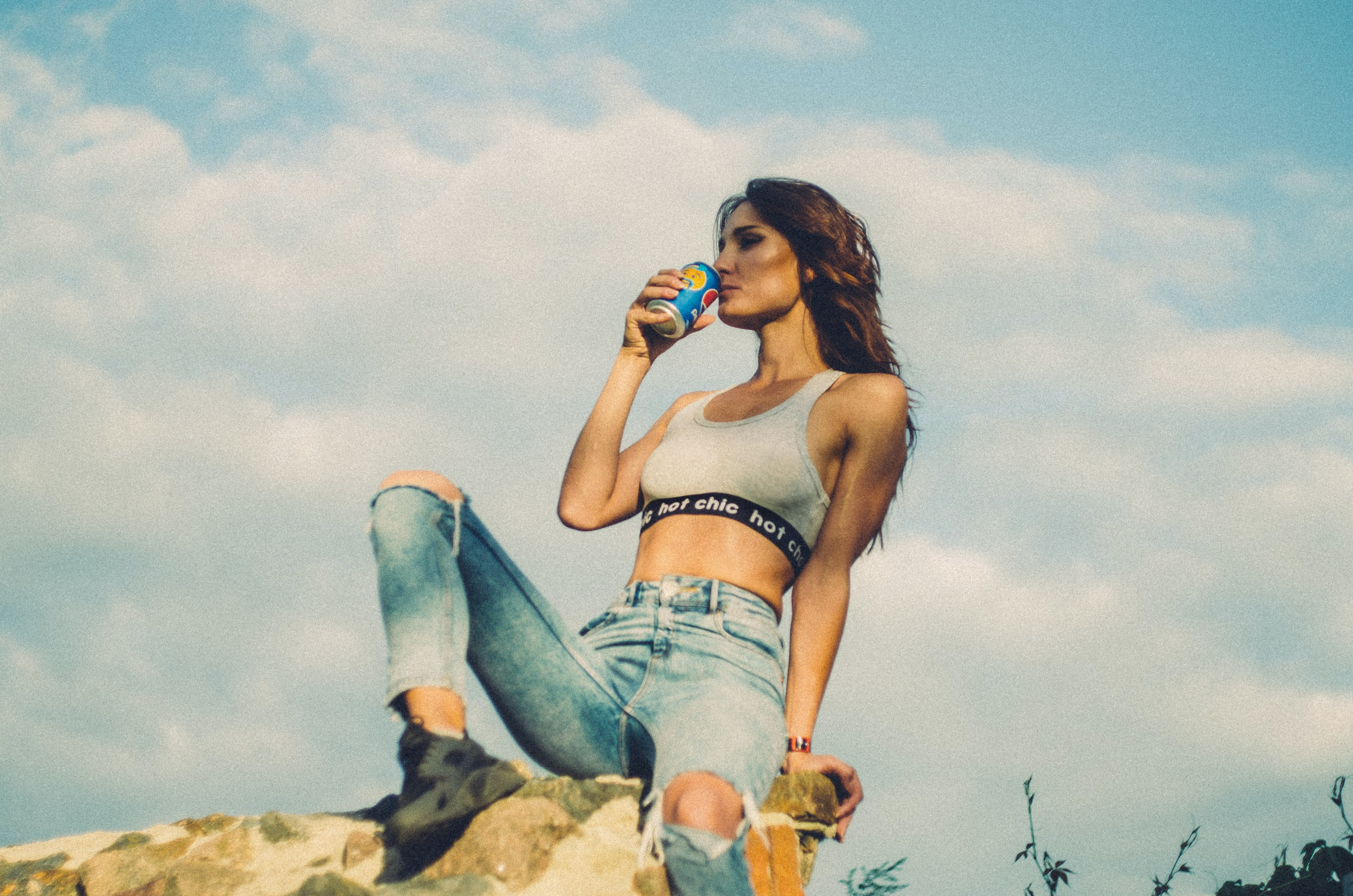 woman sitting on rocky hill drinking soda can during daytime