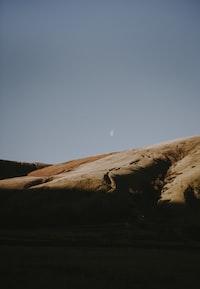 gray hill under white moon