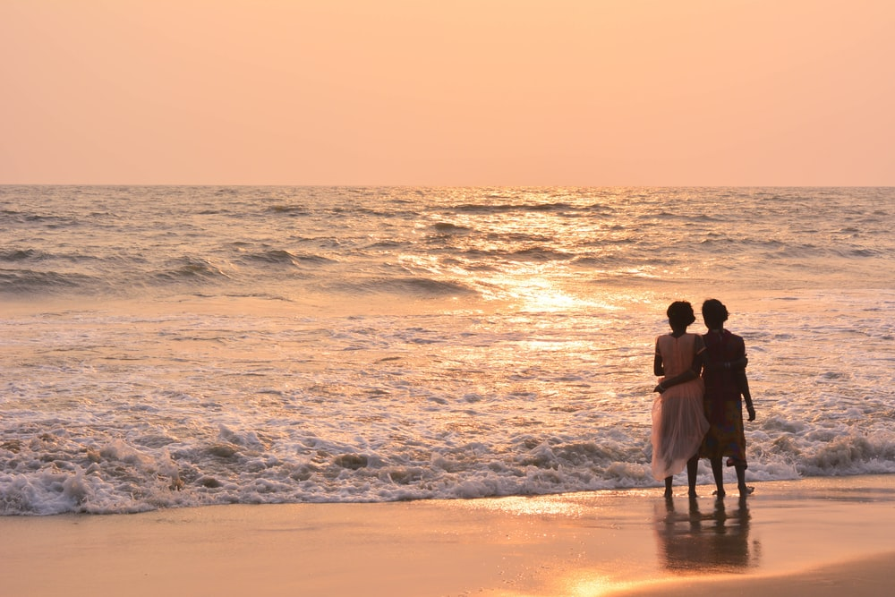 two women standing on shoreline